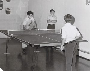 Students playing ping pong in the recreation room.