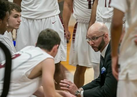 Basketball team huddling with coach.