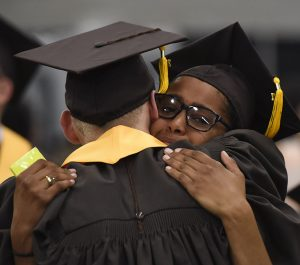 Student graduating and hugging teacher.