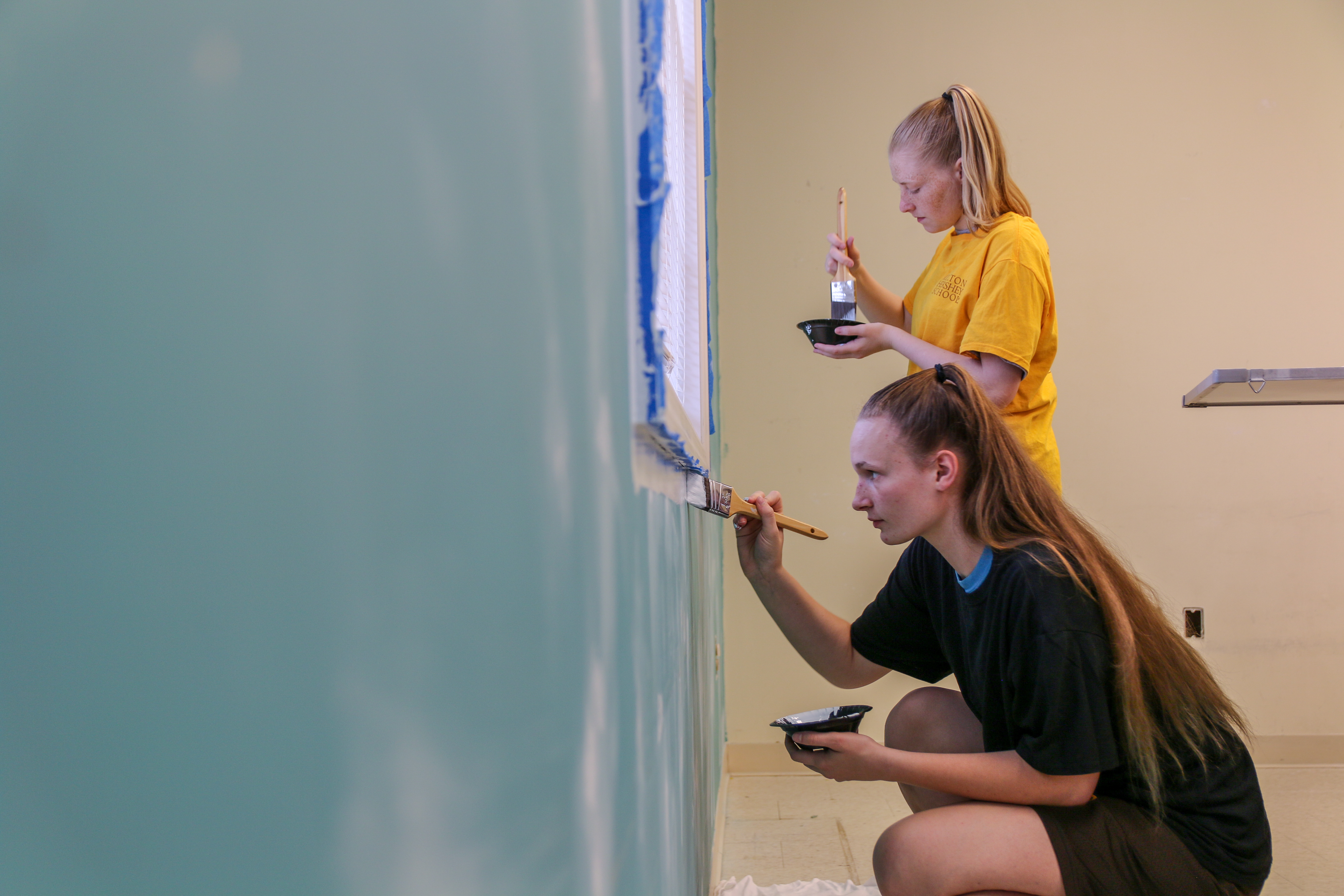 MHS students painting a wall in a community center