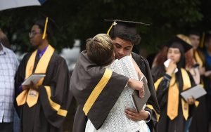 MHS graduate gives a hug after Commencement