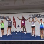 MHS junior poses on the podium after winning gold at Junior Olympics