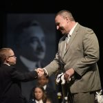 An MHS fourth-grader receives a token of achievement