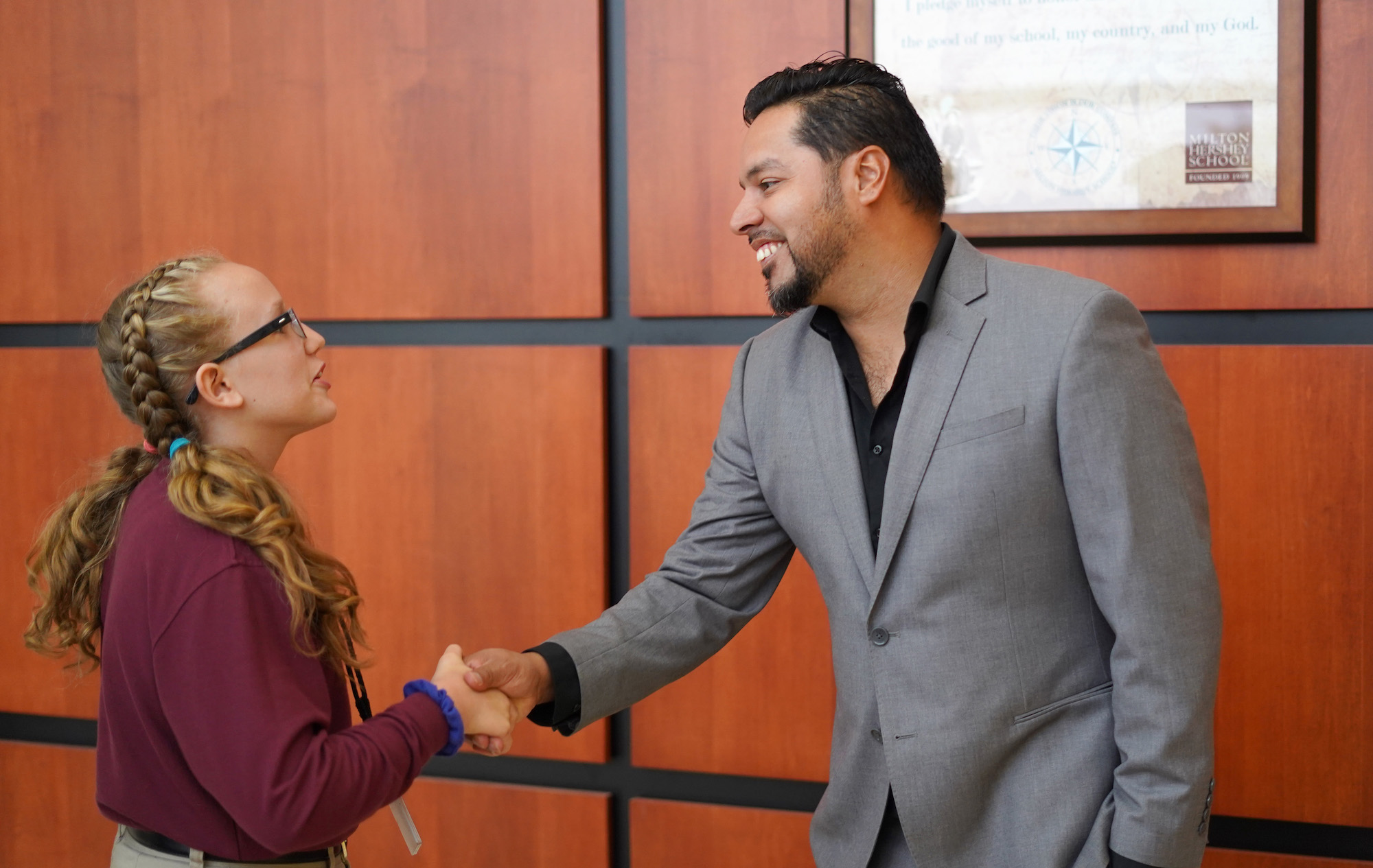 A former student of the original Freedom Writers shakes the hand of an MHS student.