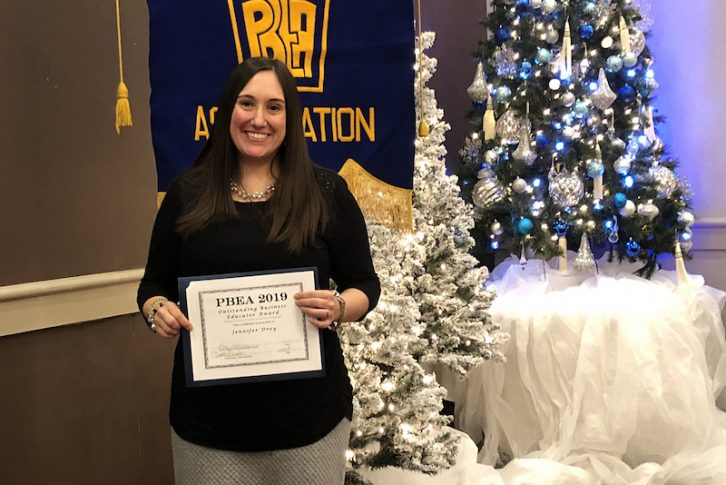 Milton Hershey School teacher Jessica Drey holds her certificate after winning PA Business Educator of the Year.