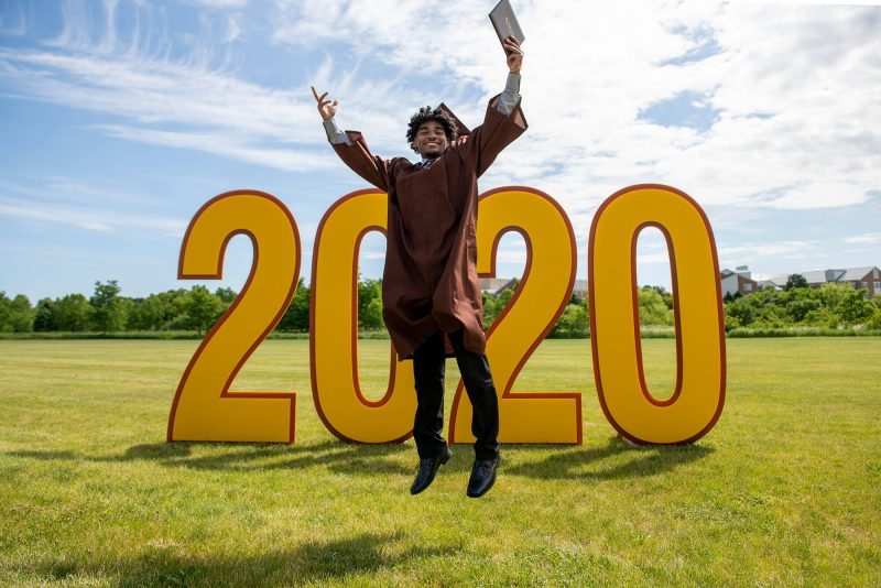 MHS graduate being photographed in front of 2020 graduation sign