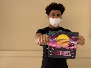 MHS student holding art canvas