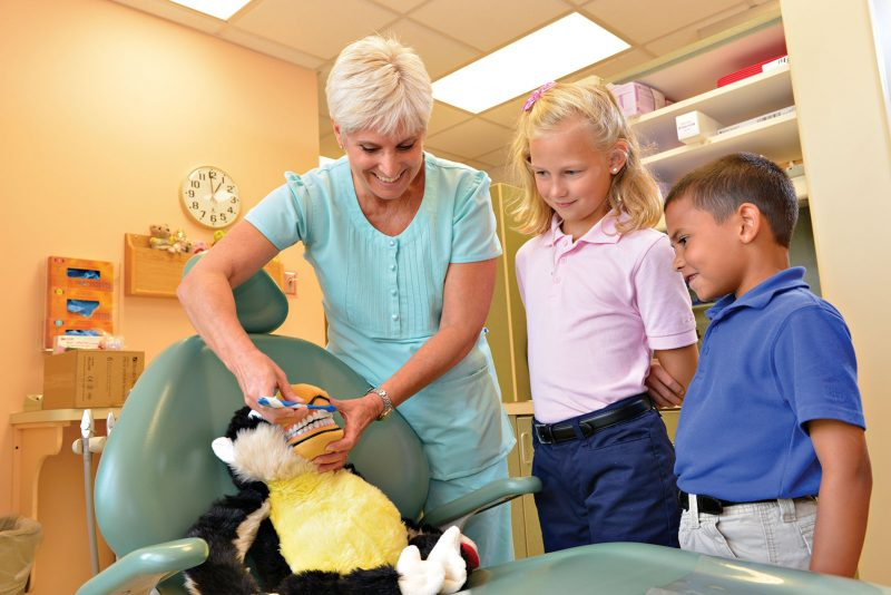 Female dentist using a toy to show two young Milton Hershey School students how to brush teeth.