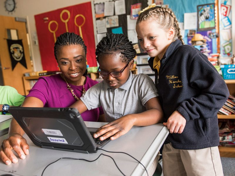 Female teacher engages two elementary school students on a tablet computer.