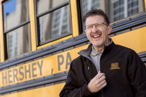 A Milton Hershey School Transportation employee smiles by a school bus at Catherine Hall.