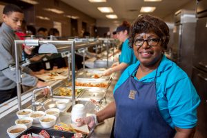 A Milton Hershey School dining services worker serves lunch to students.