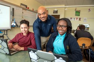 A Milton Hershey School high school teacher works with technology in the classroom.