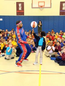 Zeus McClurkin, one of the stars of the Harlem Globetrotters, teaches a Milton Hershey School student how to spin a basketball on her fingertip.